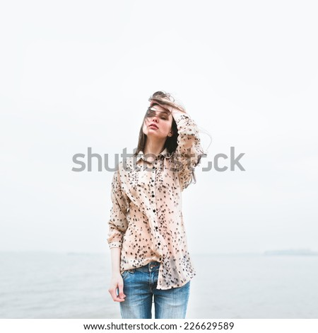 beautiful young hipster girl on the beach in a cold windy day