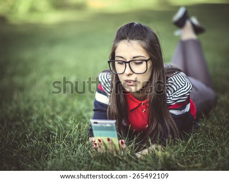 Beautiful young hipster girl using smart phone lying on the grass in the park - stock photo