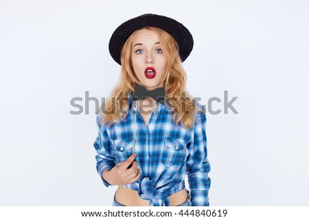 Beautiful young hipster woman surprised isolated on white background. Teenage girl in blue shirt and fashion hat shocked - stock photo