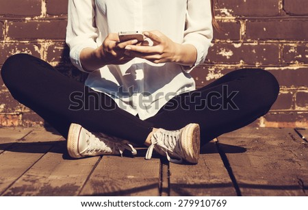 Beautiful young hipster woman using smart phone - stock photo