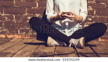 Beautiful young hipster woman using smart phone
