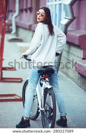 beautiful young hipster woman with bike in the city. Urban fashion lifestyle