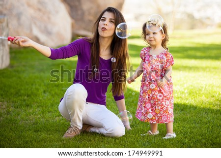 Beautiful young Hispanic mother and her baby girl having fun with bubbles outdoors - stock photo