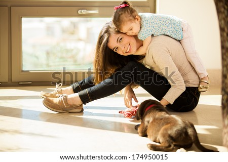Beautiful young Hispanic mother with a baby girl and a cute Labrador puppy at home - stock photo