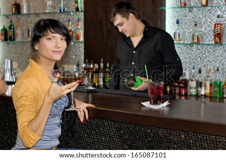 Beautiful young Hispanic woman drinking red wine at the bar turning to smile at the camera as the barman works behind the counter in the background