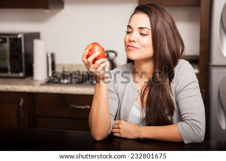 Beautiful young Hispanic woman eating an apple in the kitchen - stock photo