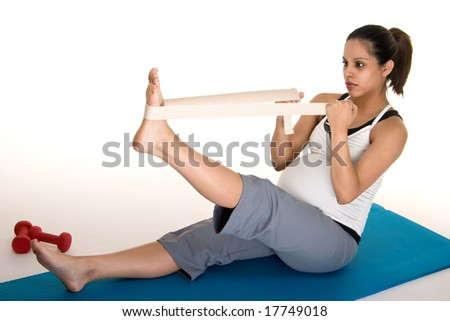 Beautiful young, Hispanic woman in a fitness workout to keep herself physically fit during her pregnancy.  Shot on white background. - stock photo