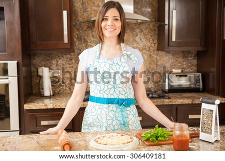 Beautiful young Hispanic woman making her own pizza in the kitchen and smiling - stock photo