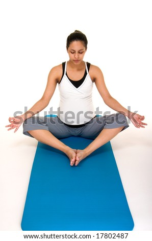 Beautiful young, Hispanic woman meditating in a yoga fitness workout to keep herself physically fit during her pregnancy.  Shot on white background. - stock photo