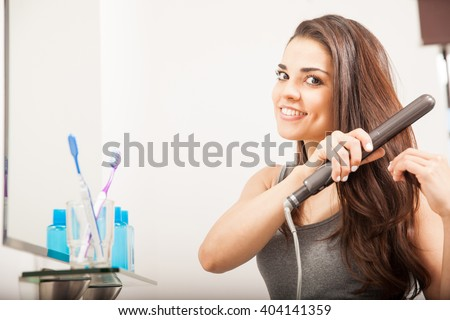 Beautiful young Hispanic woman using a flat iron to straighten her hair in the bathroom - stock photo
