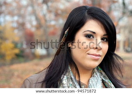 Beautiful young Hispanic woman wearing custom feather hair extensions in her black hair. - stock photo