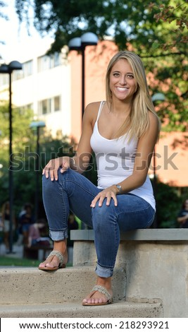 Beautiful young Hispanic woman with blonde hair wearing white tank top and blue jeans - portrait - seated