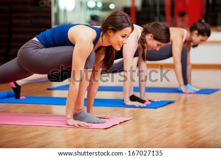 Beautiful young Hispanic women working out and enjoying their yoga class in a gym - stock photo