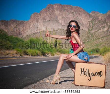 Beautiful young Hollywood hopeful hitching a lift on a desert road in California on a hot day. - stock photo