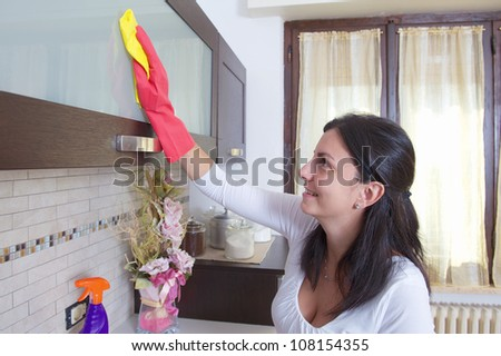 beautiful young housewife cleaning the furniture in the kitchen - stock photo