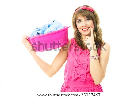 beautiful young housewife dressed in pink clothes with a basin full of clothes