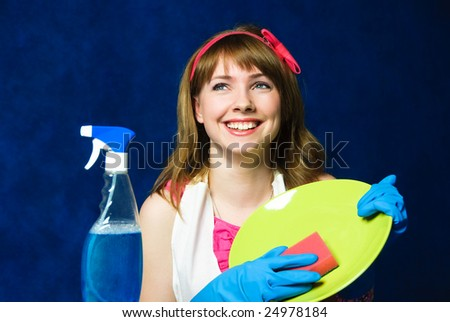 beautiful young housewife washing the dishes against blue background - stock photo