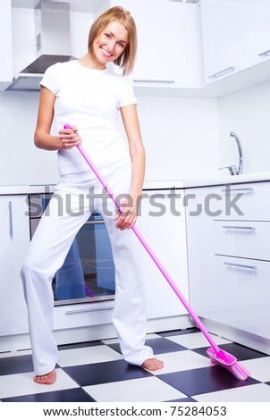 beautiful young housewife with a broom in the kitchen