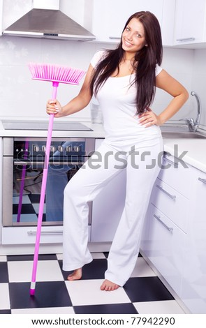 beautiful young housewife with a broom in the kitchen - stock photo