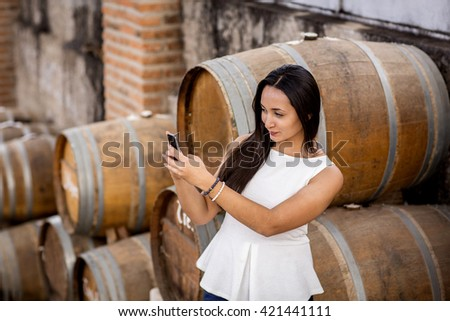 beautiful young  in wine cellar. Happy smiling  girl with smartphone mobile phone taking photo of herself - stock photo