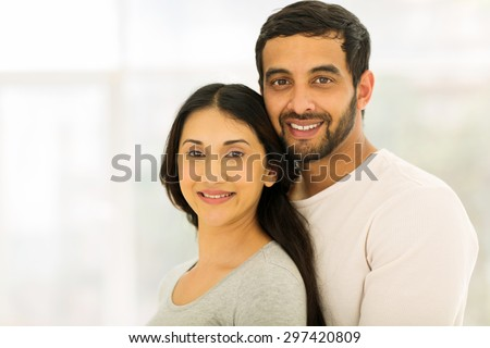 beautiful young indian couple looking at the camera - stock photo