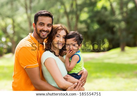 beautiful young indian family outdoors looking at the camera - stock photo