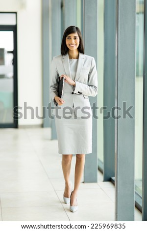 beautiful young indian office worker holding a clipboard walking in office - stock photo
