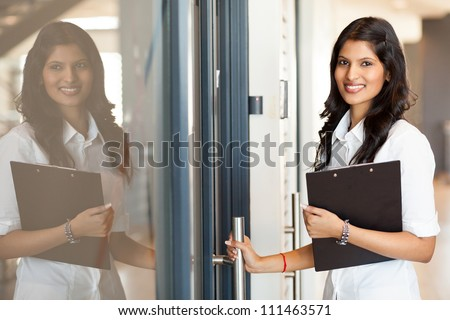 beautiful young indian white collar worker opening office door - stock photo