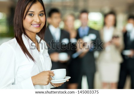 beautiful young indian woman drinking coffee during seminar break - stock photo