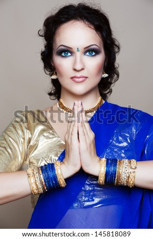 Beautiful young indian woman in traditional clothing with bridal makeup and jewelry. Bride traditionally dressed in India. Girl bollywood dancer in Sari.  - stock photo