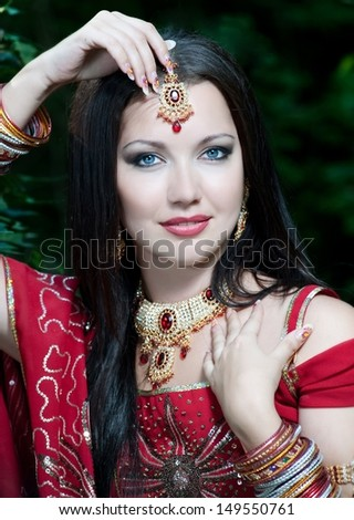 Beautiful young indian woman in traditional clothing with bridal makeup and jewelry. gorgeous brunette bride traditionally dressed Outdoors in India. - stock photo