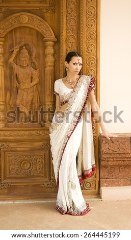 Beautiful young indian woman in traditional clothing with bridal makeup and oriental jewelry. Beautiful  bollywood dancer in Sari posing outdoor near the eastern palace. Eastern fairy tale - stock photo