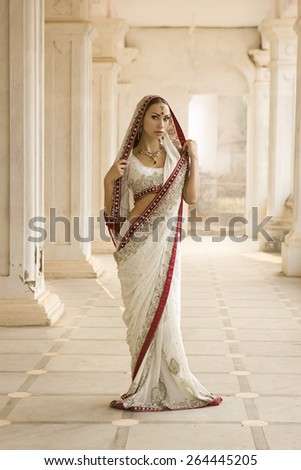 Beautiful young indian woman in traditional clothing with bridal makeup and oriental jewelry. Girl bollywood dancer in Sari posing outdoor near the eastern palace. Eastern fairy tale  - stock photo