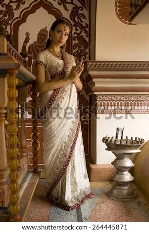 Beautiful young indian woman in traditional clothing with incense  makeup and oriental jewelry. Girl bollywood dancer in Sari, eastern palace. Beautiful princess praying. Eastern fairy tale - stock photo