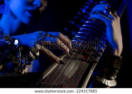Beautiful young indian woman in traditional clothing with sitar and oriental jewelry. Beautiful bollywood Girl playing the sitar (blue lens effect) - stock photo