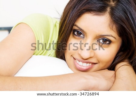 beautiful young indian woman on bed - stock photo
