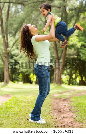 beautiful young indian woman playing with baby boy outdoors - stock photo