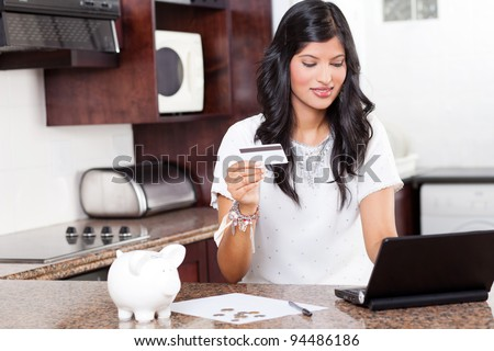 beautiful young indian woman using credit card shopping online - stock photo