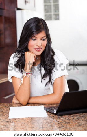 beautiful young indian woman using laptop computer at home - stock photo