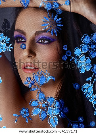 Beautiful young Italian woman with artistic blue eyeshadow and long hair behind the blue flower lace net, shot in low key . - stock photo