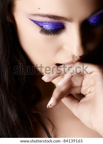 Beautiful young Italian woman with artistic purple eyeshadow and long hair looking down and biting her hand, shot in low key. - stock photo