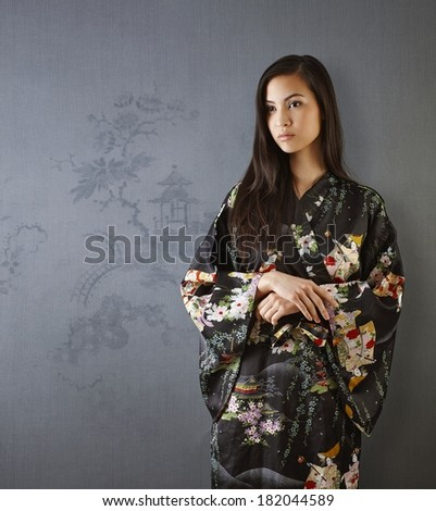 Beautiful young Japanese woman standing by grey wall, looking away, wearing kimono.