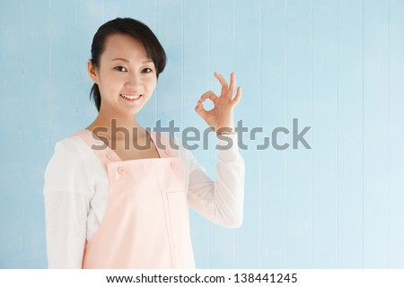 Beautiful young japanese woman to make a finger, blue tiled background with copy space. - stock photo