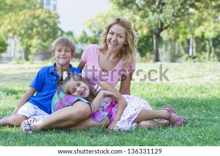 Beautiful young lady and her cute children posing in the green park at bright summer day - stock photo