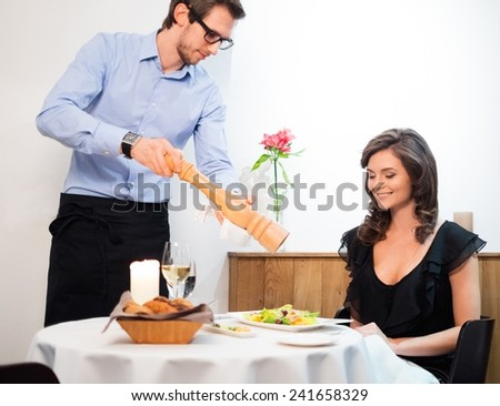 Beautiful young lady and waiter in restaurant  - stock photo