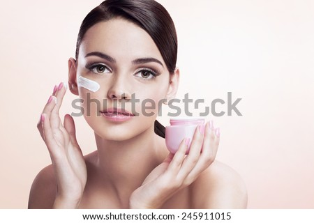 Beautiful young lady applying moisturizing creme, skin care concept / photoset of attractive brunette girl on beige background  - stock photo