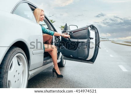 Beautiful young lady came out frome her car on the road - stock photo