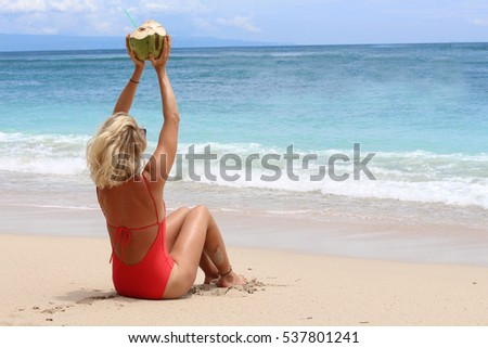 beautiful young lady drinking coconut on a beach in Bali