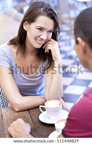 Beautiful young lady having conversation with young man over a cup of coffee - stock photo