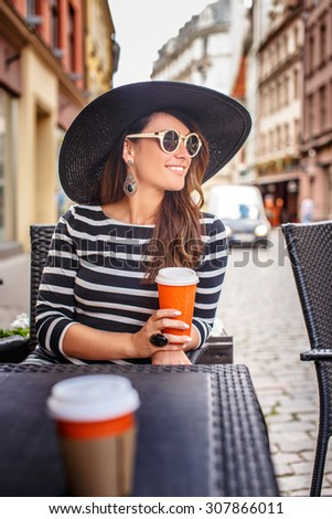 Beautiful young lady in big summer hat and in dress with stripes drinking coffe outside in summer cafe - stock photo